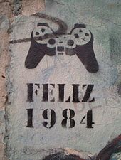 """Happy 1984"" stencil graffiti, denoting mind control via video games, on a standing piece of the Berlin Wall, 2005."