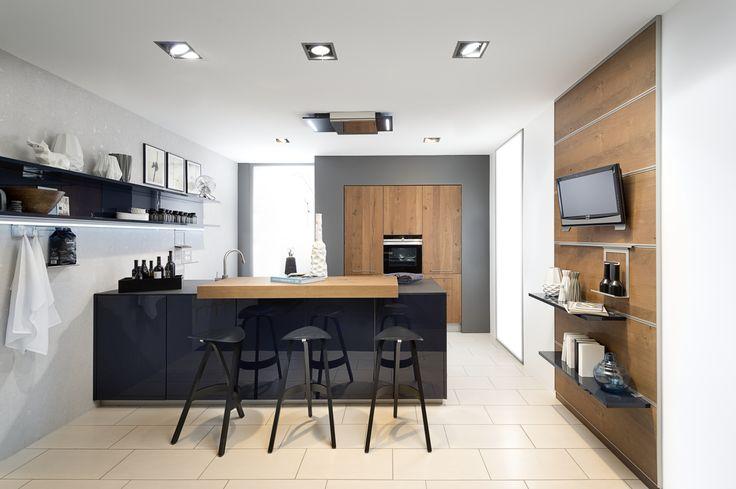 Kuchnia NOLTE w stylu nowoczesnym. Efektowne połączenie dębowego forniru i głębokiego granatu w połysku  Dwa typy półek - tradycyjne naścienne oraz w formie modułowych paneli naściennych.