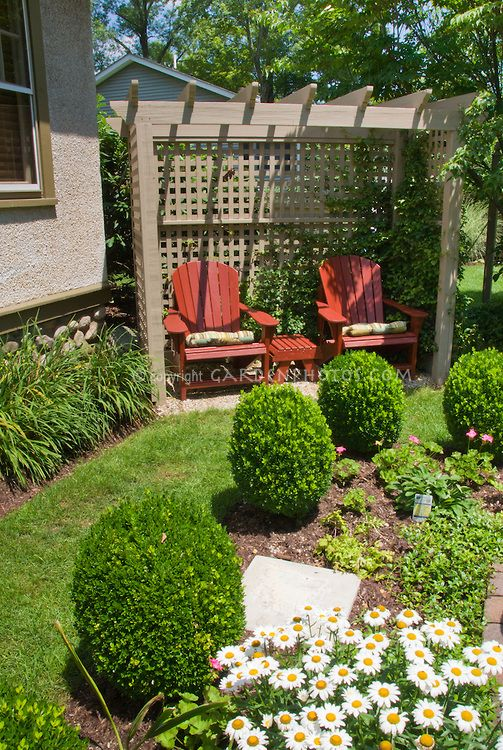 Pic: English formal style garden scene with house, covered garden bench swing and trellis