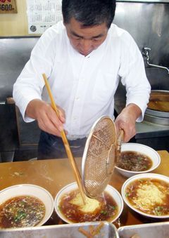 """Menya Musashi: """"The cooks are animated in the open kitchen, with the head noodle chef constantly yelling as he pulls noodles from boiling water. . ."""""""