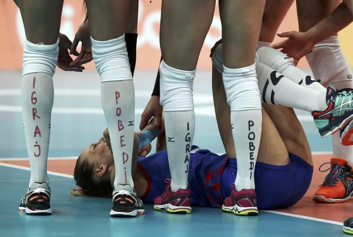 2016 Rio Olympics - Volleyball - Women's Gold Medal Match China v Serbia - Maracanazinho - Rio de Janeiro, Brazil - 20/08/2016. Serbia's (SRB) players check on teammate Maja Ognjenovic (SRB) of Serbia after she was hit in the face by the ball. REUTERS/Ricardo Moraes