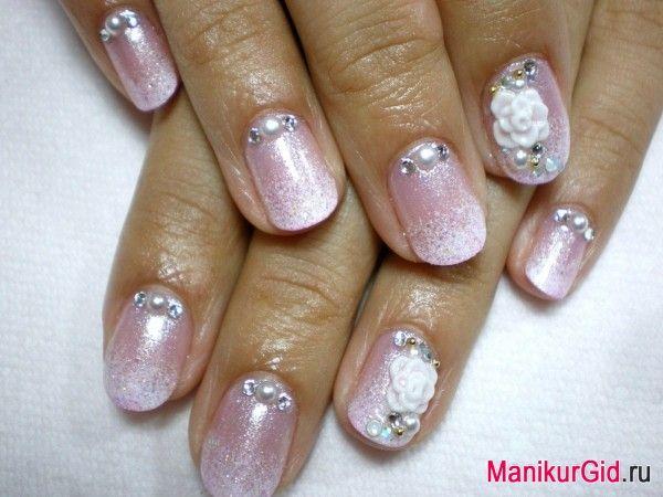 Ледяные цветы: основной фон маникюра выполнен перламутровым лаком холодного розового оттенка. Кончики ногтей покрыты бело-сребристым шиммером. Ногти безымянных пальцев украшены белыми керамическими цветами, бусинами и стразами.