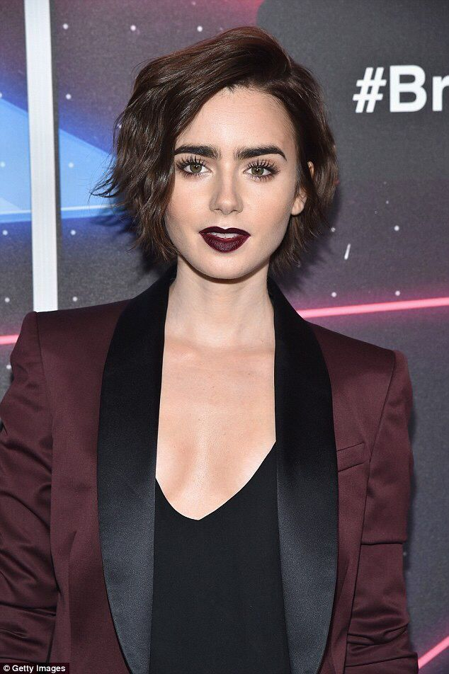The lady is a vamp! Lily Collins goes from drab to glam swapping grey pilates leggings to rock a retro burgundy trouser suit and matching lippy at awards show in LA
