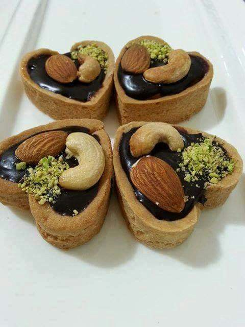guessing at this one - using a sable dough,cut heart shapes; for half of them cut smaller heart shapes in middle of half the big hearts and discard centres. Place the cutout shape on top of the whole heart shape binding w/egg wash. Bake. Fill with choc ganache; add whole almonds, cashews & chopped pistachios. (photo only)