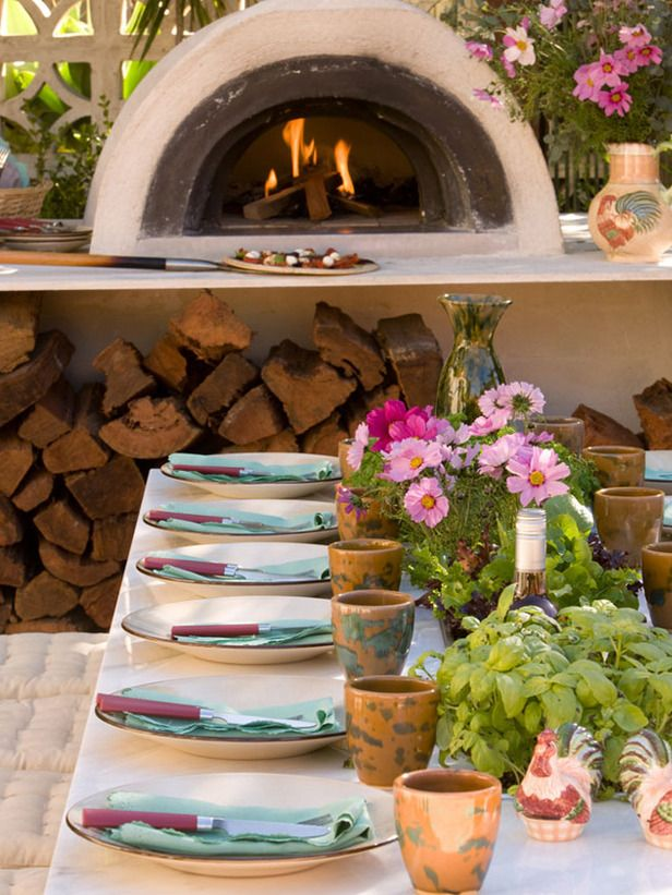 Tuscan Influence  Designer Jamie Durie enhanced the feel of this Tuscan-inspired patio by adding a wood-fired pizza oven as the space's focal point. Accompanied by a large, bench-style dining table and conversational seating, this warm outdoor space is ready for guests.
