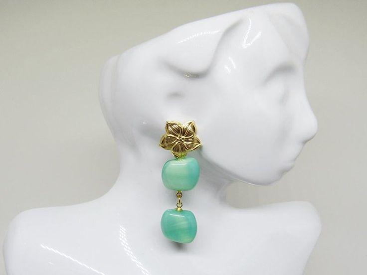 Brinco Hibisco Verde   Um brinco clássico, feito com uma linda base em formato de flor de hibisco, é antialérgica, folheada a ouro 18k e livre de níquel em sua composição.   Seu pingente é composto por contas de vidro prensado verde aqua, compradas em Londres. As contas possuem um formato de 'almofadinha', são quadradas e contorcidas.