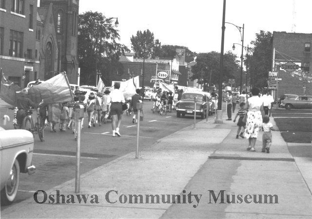Oshawa's Neighbourhood Parks Parade  Black and White photo of Oshawa's Neighbourhood Parks Parade going south on Simcoe Street South and passing Bruce Street  To the left is St. Andrew's United Church.