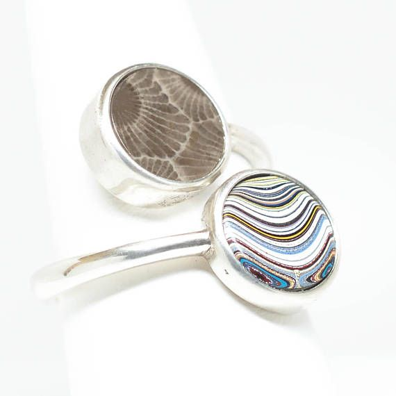 This ring is a size 8.25. Beautiful two stone Sterling Silver ring with Petoskey Stone and Fordite. Each stone is 10mm in diameter. The ring band width is 2.8mm. This is not a a sample. The ring pictured is the exact one you will receive. Petoskey Stone is a fossilized coral.