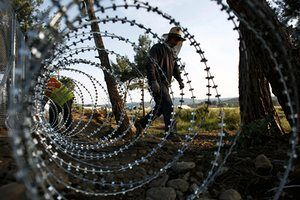 Workers put up a barbed wire fence in Idomeni parallel to the railway tracks, which have been blocked by refugees and migrants for more than a month