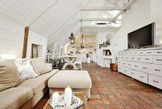 amenagement comble sol en briques rouges, canapé beige, meubles en bois clairs, plafond en bois
