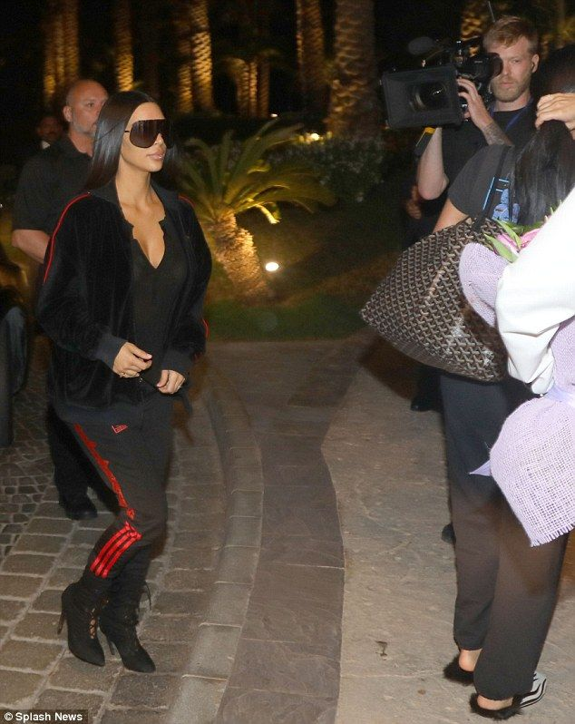 Sporty chic: The star wore the tracksuit pants from the collection with a velour and red piping zip up jacket and lace up stiletto boots