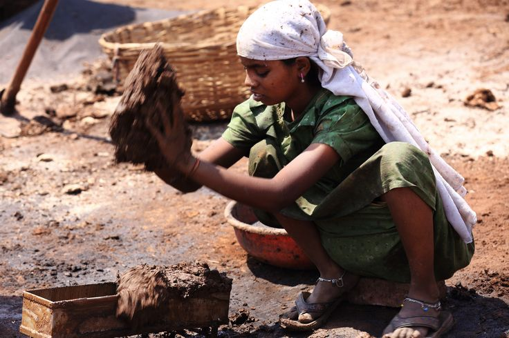 Fazendo tijolos de barro. Uma mulher indiana trabalha colocando lama em um molde e, em seguida, expondo para que ele seja aquecido pelo sol. Não é necessariamente o material de construção mais forte. Muitas aldeias têm suas construções feitas com estes tijolos 'derretidas', e em regiões rurais houve estruturas que cederam ou caíram. A foto foi feita na vila de  Bhosalewadi, próximo a Karad, estado de Maharashtra, na Índia.  Fotografia: Sayid Budhi (DocBudie) no Flickr.