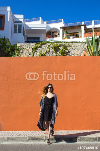 Beautiful girl model standing in front of a colorful wall in the summer scenery