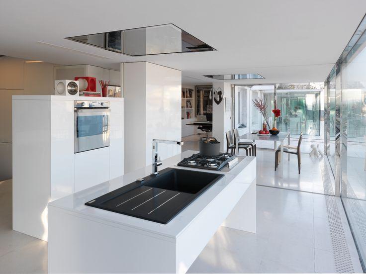El fregadero negro es sofisticación, fuerza y dureza en contraste con los muebles y paredes blancos.
