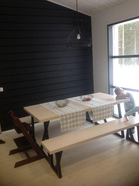 Puuseppäopiskelija toteutti kuuden hengen ruokapöydän visiomme mukaan. . Lamppu ja kaitaliinat Elloksen. Ruokailutilassa ja olohuoneessa on ulkovuorilaudasta tehty musta seinä