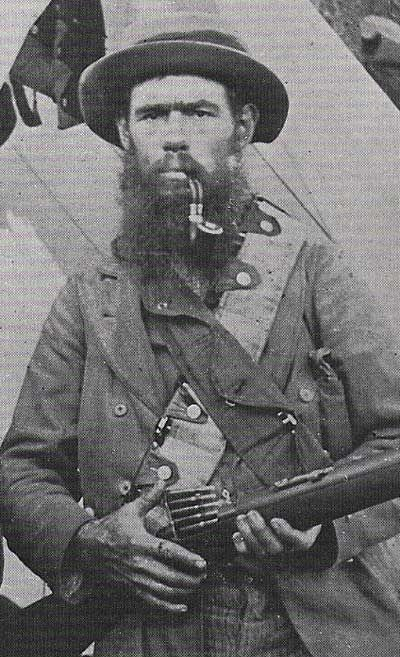 Boer in a favourite photographic pose of the day, a press of the thumb and five Mauser bullets are loaded at one go....