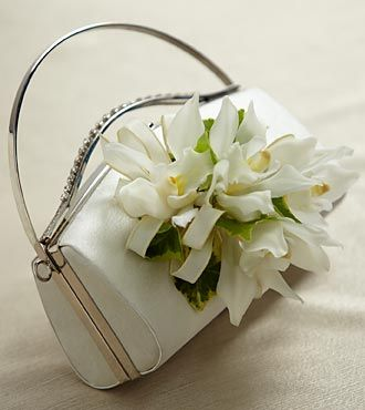 The FTD® White Purse Décor turns your simple wedding clutch into a memorable accessory. Mini Cymbidium Orchid stems are arranged with variegated ivy vines and accented with an ivory taffeta ribbon to create a wonderful way to add that extra touch to your wedding day.