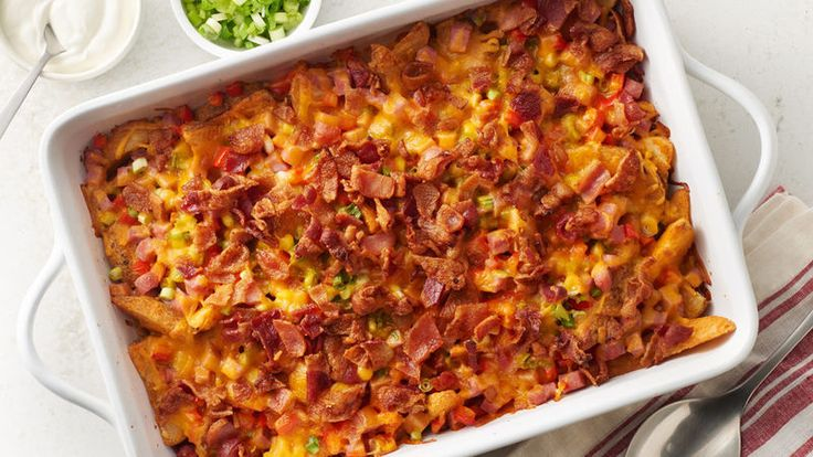 An amazing cheesy potato casserole topped with ham, red bell pepper, green onions, bacon and cheese.