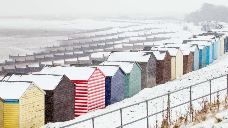 Colourful beach huts on the beach. The whole scene is covered in snow.