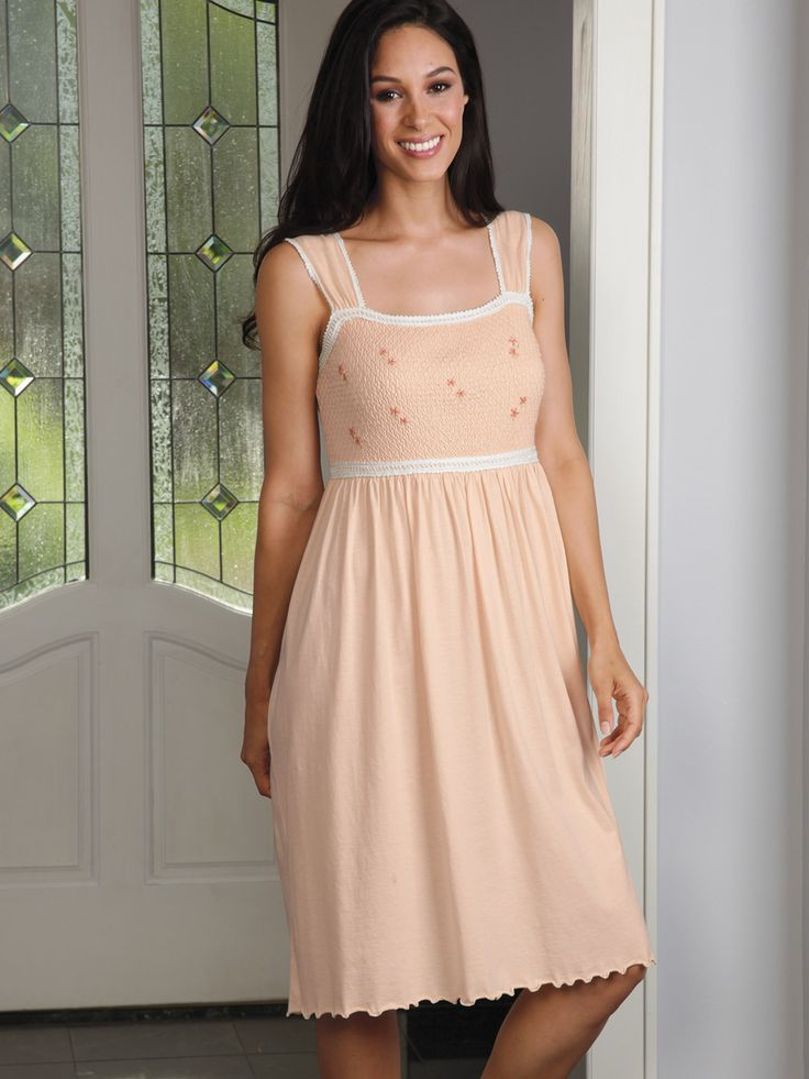 Imported from Peru, this peach gown with lovely lace borders, is both coy and cunning. The bodice, which is hand smocked for added elegance and...