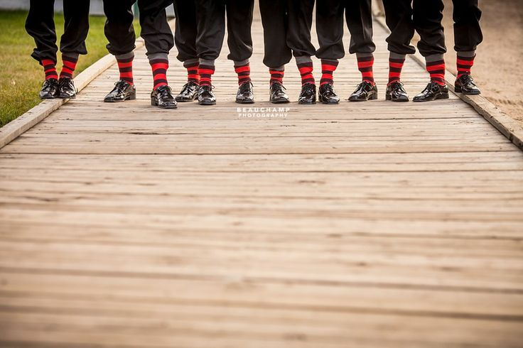 Unique striped red and black socks on Groom and Groomsmen, standing on the wood sidewalk at Fort Edmonton Park. See more images from this wedding by Beauchamp Photography at: https://www.facebook.com/media/set/?set=a.736453626382891.1073741851.149173701777556&type=3