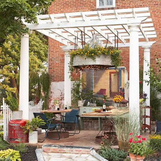 A Pergola with Personality! Part sculpture, part light fixture, a massive overhead structure offers support for illumination and blooms while the existing brick wall of the house teases the eye with a bit of trompe l'oeil painting. (Better Homes  Gardens)