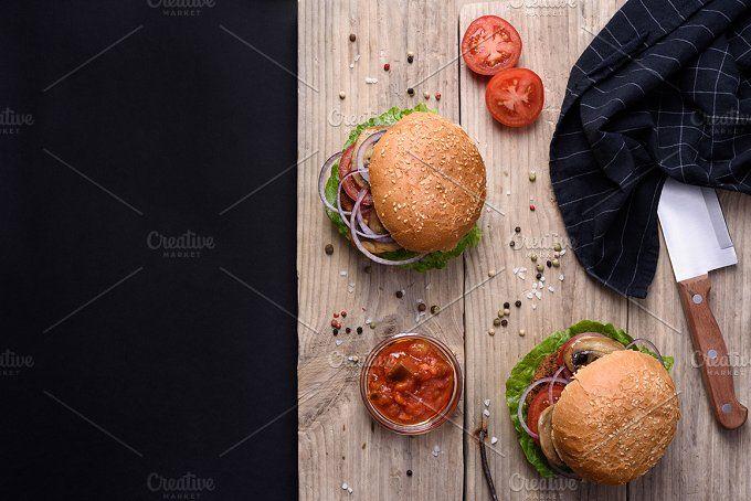 Burgers on wooden board. by Iuliia Leonova on @creativemarket