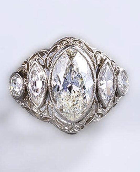 A belle époque diamond ring, circa 1910 centering a marquise-shaped diamond flanked by smaller marquise-shaped and round brilliant-cut diamonds all within a delicately engraved openwork mount; central diamond weighing approximately: 2.75 carats; mounted in platinum;