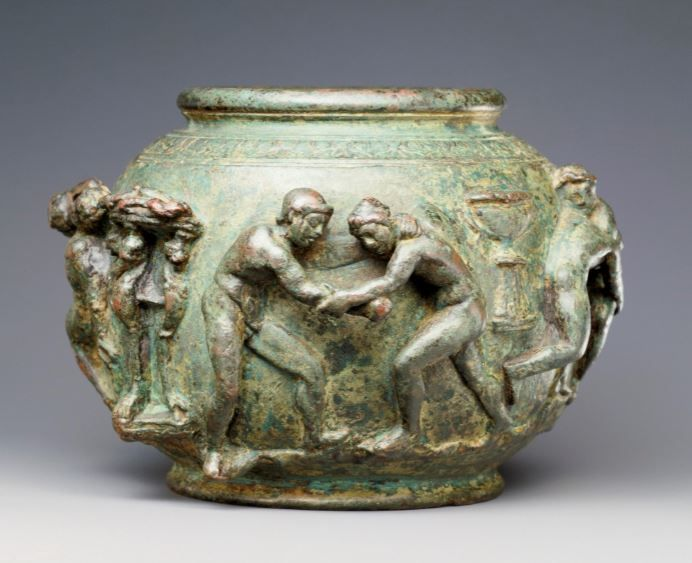 Roman situla with a frieze of athletic contests, Gallo Roman, 75-100 A.D. Encircling the round body of this bronze situla, nude athletes, boxers, and wrestlers compete fiercely under the supervision of a judge who carries palm branches and a wreath. Prizes, a kantharos or cup, basins on stands, and wreaths, are displayed between the groups of figures, 9.5 cm high. Getty museum