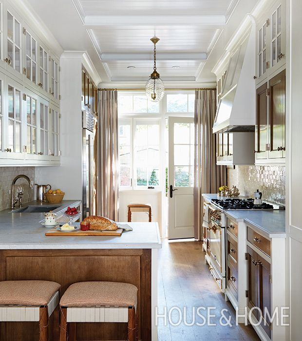 This galley kitchen is fitted with cabinets with glass-paned uppers and walnut-panelled lower cabinets that add warmth and contrast. | Photographer: Michael Graydon | Designer: Silvana D'Addazio