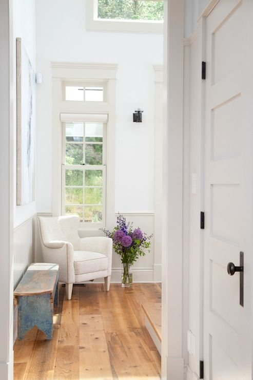 Gorgeous entryway with wide planked hardwood floors and white walls with glossy off white trim. The room features an ivory colored armchair in the corner beneath the window. A vase of purple and blue flowers stands beside the chair. A large frameless abstract hangs on the wall beside the chair with a distressed blue bench beneath.