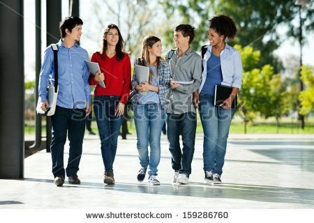 Full length of happy college students walking together on campus - stock photo