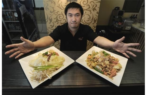Tony Ungpakawa, co-owner of Million Thai Restaurant, 4109 118th Ave., with plates of pad thai hor kai and pineapple fried rice