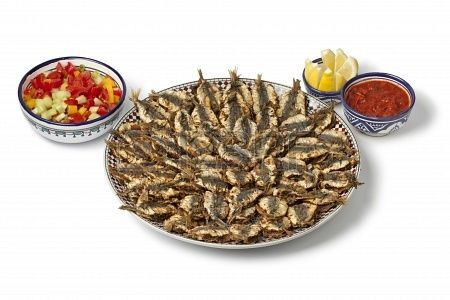 Dish with Moroccan fried stuffed sardines on white background