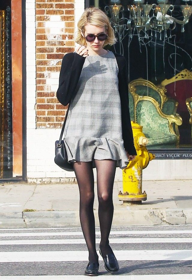 Emma Roberts wears a plaid mini dress over a long-sleeve tee, tights,  black shoulder bag, oxfords, and round sunglasses