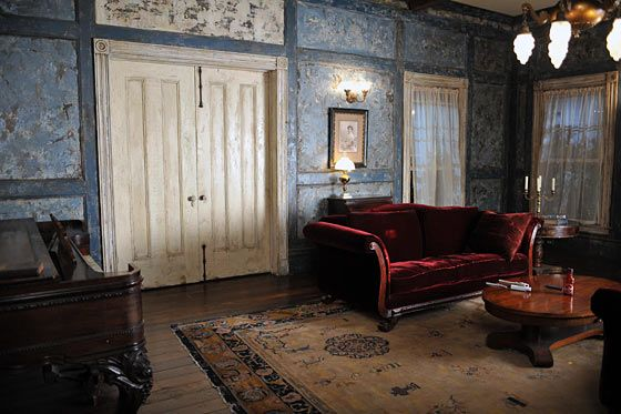 In Season One Bill's home in Bon Temps looks worn from years of neglect. Peeling paint, gauzy drapes, and a wine-red velvet sofa create a ghostly feeling in the space. #trueblood #halloween