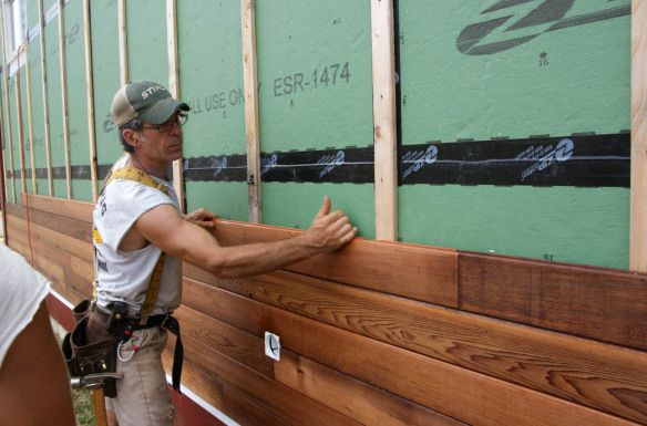 Adam installing stained tongue and groove red cedar siding
