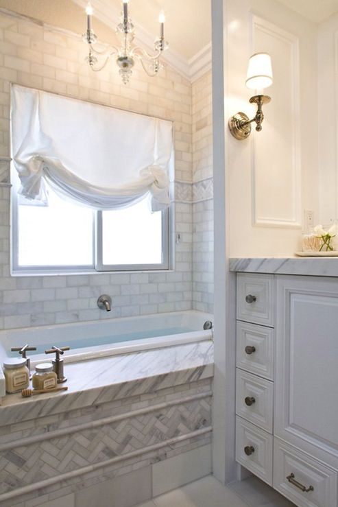 Chic master bath with marble herringbone tiles, white bathroom vanity with marble counter top, marble subway tiles bath surround, white shade and lucite acrylic chandelier.
