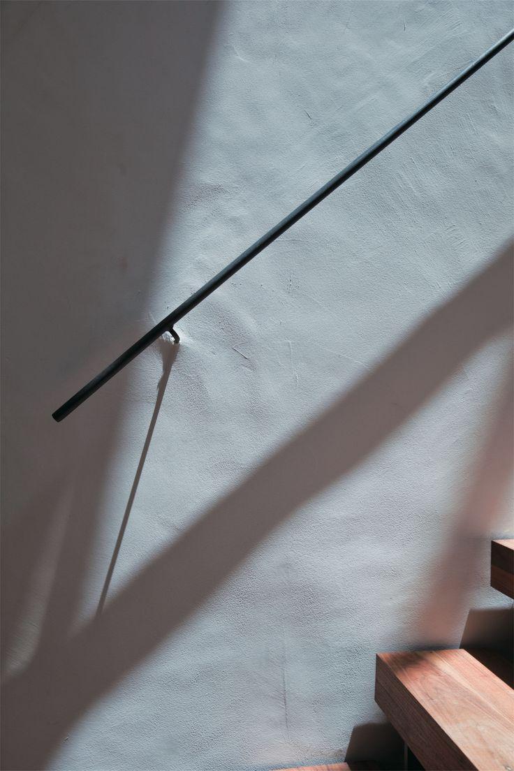 ロートアイアンで作ったシンプルな階段手すり。イタリア漆喰の壁。