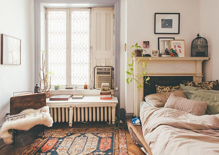 Cozy bedroom with a colorful rug, pretty bedding and a perfect mantle.