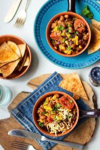 Deze chili con carne met mais bevat lekker veel kruiden, verschillende soorten bonen en is heerlijk met wat knapperige tortillachips, kaas en verse peterselie.