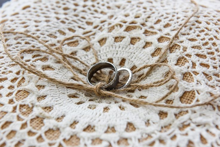 Wedding rings on a vintage lace pillow tied up with brown string for boho wedding. Photographed by Anais Photography