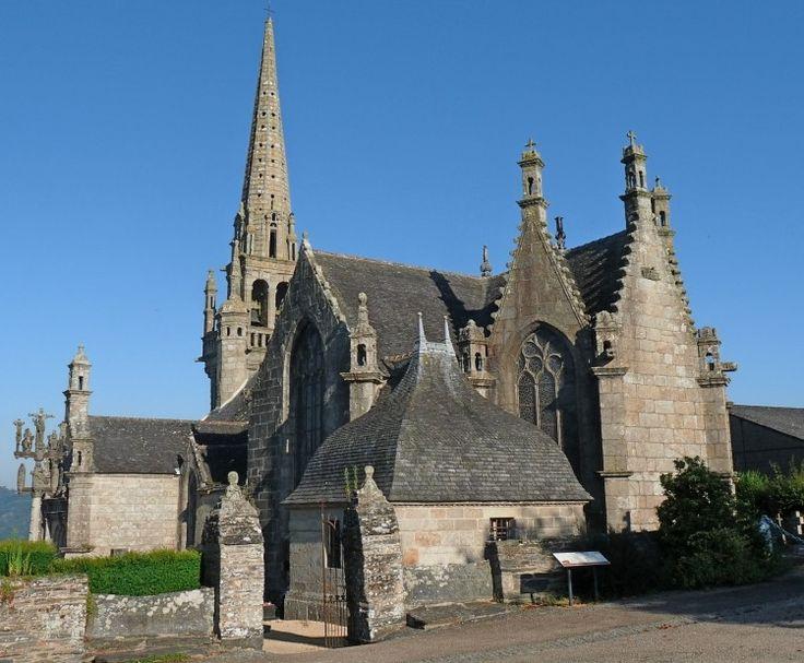 Patrimoine - Locmélar - Vue d'ensemble de l'enclos paroissial  En arrière de la porte d'entrée de l'enclos matérialisée par deux piliers surmontés d'ornements sculptés, on peut découvrir les éléments constitutifs d'un enclos paroissial: l'église depuis le clocher de 1589 au fond, jusqu'au chevet de 1681 à droite de la photographie ; le calvaire et le porche surmonté d'un lanternon ; la sacristie, particulière par sa toiture en carène de bateau retournée.