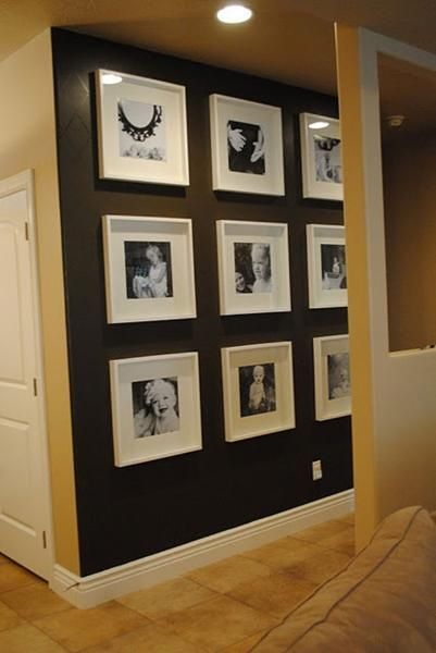 Family photographs framed in nine square white frames and mounts on a dark wall