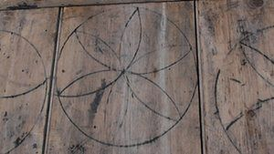 Witches' marks on a barn door in Laxfield, Suffolk. The marks coincide with a period when most interiors lit by rush lights or tallow candles would have been extremely dark once night fell, and when belief in witchcraft and trials of unfortunates accused of it were at their height.