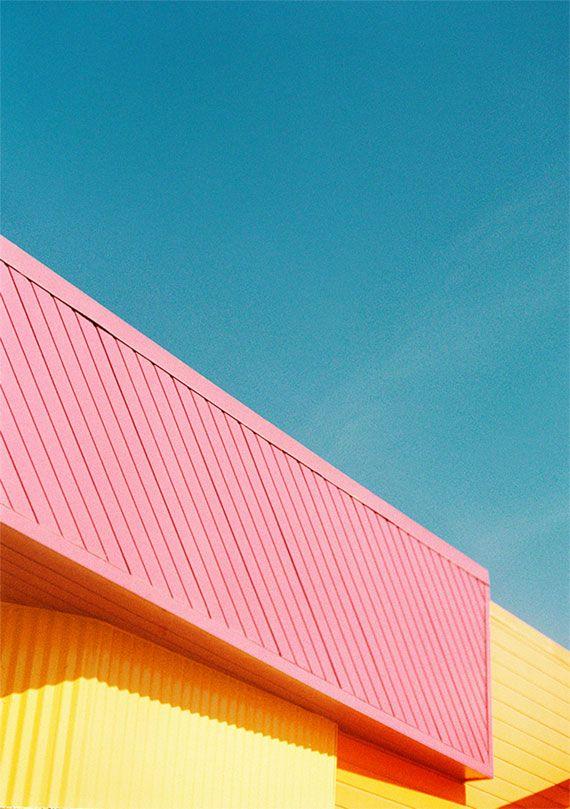 Lichte pastelkleuren van een gebouw tegen de lichte blauwe hemel, die enkele witte tinten in zich heeft verspreid.