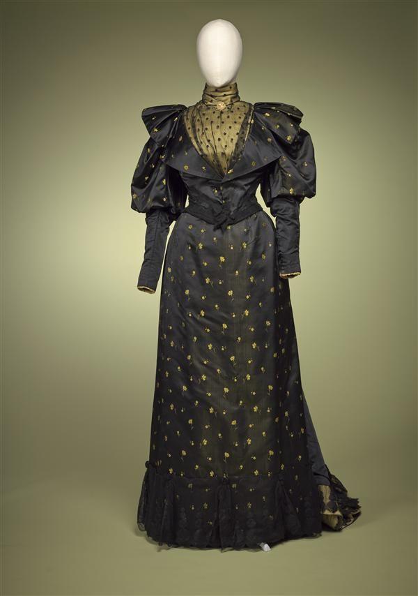 Namiddagjapon van zwart satijn, met ingeweven geel bloemetje; garnering van zwarte tule en gele satijn, bestaande uit lijfje en rok