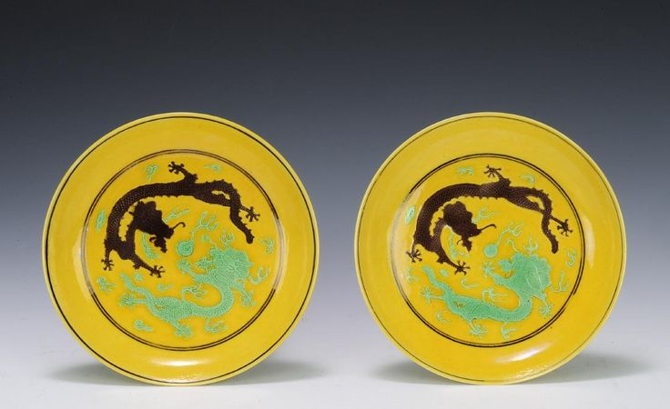 Pair of imperial Sancai plates with a Tongzhi mark and of the period. The plates are yellow ground with one purple five-clawed dragon and one green five-clawed dragon on the facades. The dragons are depicted amongst the clouds, chasing a flaming pearl. The undersides are painted with four cranes and clouds in green. The plates both have six-character Tongzhi marks.