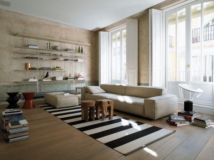 Una sequenza di balconi dalle eleganti modanature illuminano il soggiorno con libreria di Molteni, divani disegnati da Piero Lissoni per Living Divani, tavolini colorati di Minotti, tappeto Kasthall, lampada Taccia di Flos.