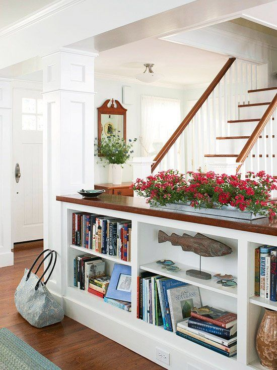 Divide a kitchen and living room with a bookcase topped with flowers